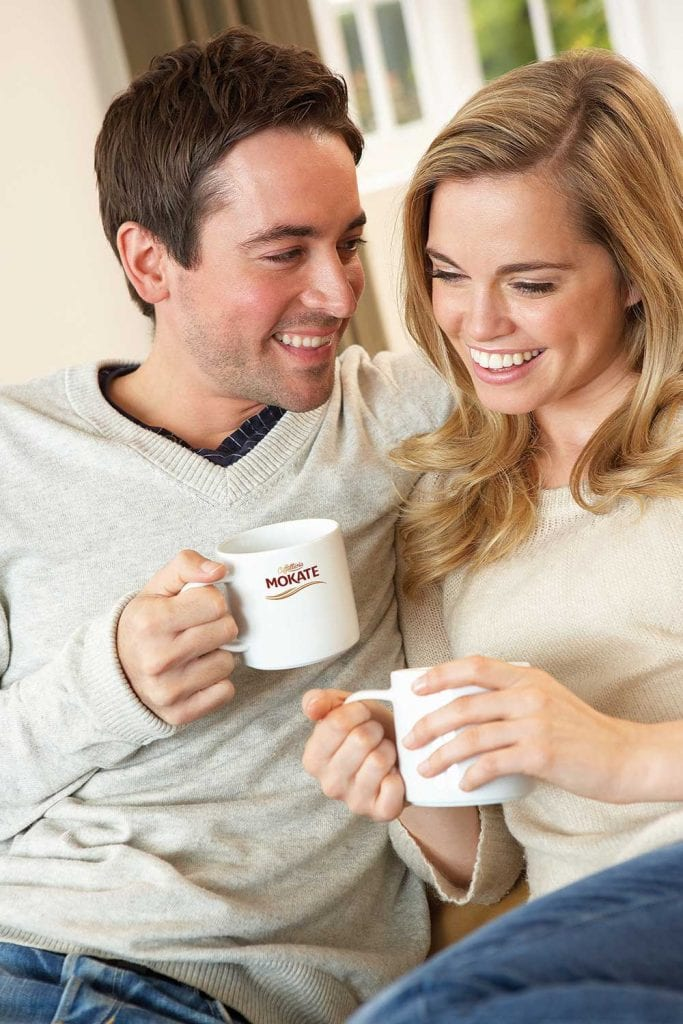 Happy couple drinking from mugs