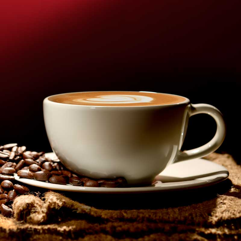 Coffee in a white cup with roast coffee beans